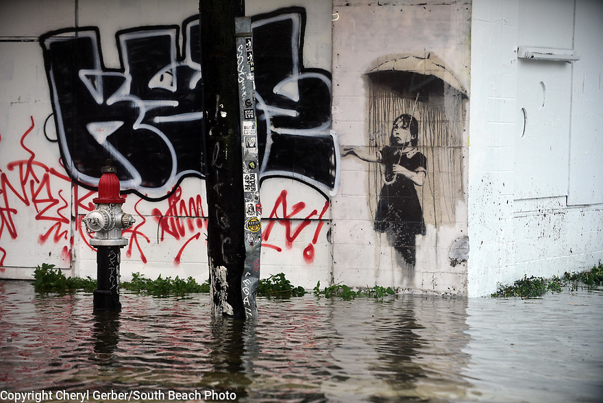 """""""Rain Girl"""" by renowned graffit artist Banksy is swamped by heavy rains flooded streets and businesses ahead of Tropical Depression Barry, which is expected to make landfall as a Category 1 hurricane on Sat., in New Orleans, Wed., July, 10, 2019."""