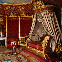 In Empress Josephine's bedroom a circle of painted sky is revealed at the top of the faux red silk tent. The bed is by Jacob Desmalter and a portable writing desk adds to the illusion that the room is part of a military camp