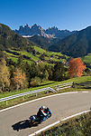 Italy, South Tyrol, Alto Adige, Dolomites, Val di Funes: mountain village St. Magdalena and Le Odle mountains at natural park Puez-Odle, rural road, bike