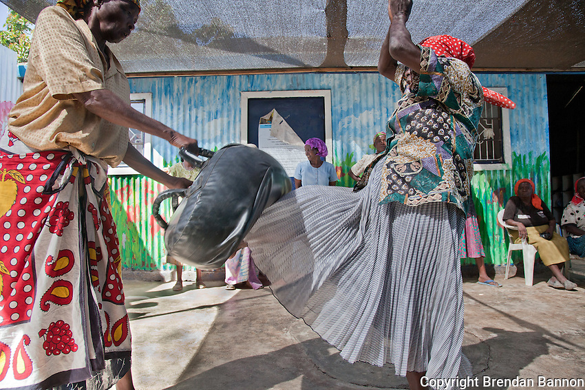 """Gender Defender coach Beatrice Nyariara (r), 68-years-old, demonstrates a self defence kick to the groin of her """"assailant."""" She advised the self defence class for women """"make sure you don't miss the potatoes."""""""
