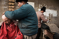 Uighur barbers shave clients in an alley on the outer edge of the Old City section of Kashgar, Xinjiang, China.