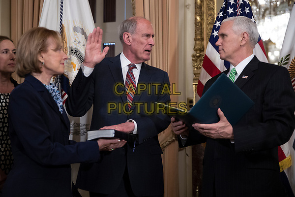 United States Vice President Mike Pence (R) administers the oath of office to Director of National Intelligence Dan Coats (C), with his wife Marsha Coats (L), during a swearing in ceremony in the US Capitol in Washington, DC, USA, 16 March 2017.<br /> CAP/MPI/RS<br /> ©RS/MPI/Capital Pictures