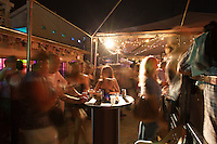 Group of friends enjoying a drink at an outdoor rooftop bar laughing and chatting around a table.