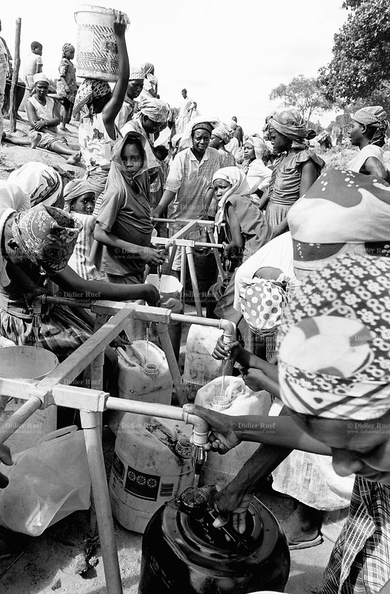 Mozambique. Province of Gaza. Chaquelane. Camp for displaced people from the town of Chokwe which was heavily flooded by The Limpopo river. Women and children fill up water containers. © 2000 Didier Ruef