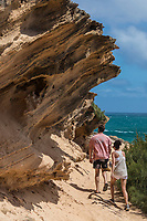 A man and a woman hike the Maha'ulepu Heritage Trail, Po'ipu, Kaua'i.