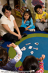 Preschool Headstart 3-5 year olds circle time female teacher working with group on letter sounds vertical