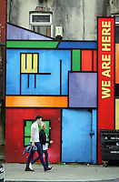 WORDS BY KARL WEST<br /> Pictured: A couple walk outside a building emblazoned with a 'We Are Here' slogan Friday 30 September 2016<br /> Re: The regeneration of the High Street in Swansea, Wales, UK