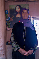 Morocco.  Amazigh Berber Woman with Mona Lisa Decorating her Room, Ait Benhaddou Ksar, a World Heritage Site.