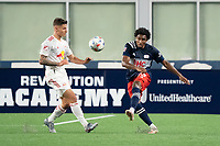 FOXBOROUGH, MA - MAY 22: Jon Bell #22 of New England Revolution passes the ball forward during a game between New York Red Bulls and New England Revolution at Gillette Stadium on May 22, 2021 in Foxborough, Massachusetts.