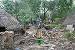 A woman standing in the middle of the debris of her home. Nagapattinam.India.
