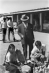 San Cristobal de las Casas 1970s Mexico. Elderly man has servant  to buy fruit for him from Indigenous young Indian girls with a baby selling in the daily market. 1973 Mexican State of Chipas