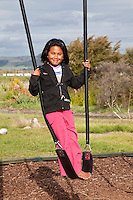 Seven-year-old Maori Girl on Swing, Ohinemutu Maori Village, Rotorua, north island, New Zealand.