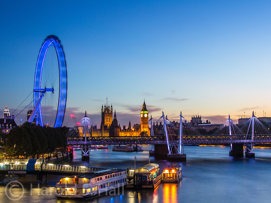 The London Eye is a 443 foot tall Ferris wheel along the River Thames in London. Big Ben is seen in the back ground of this photo captured at dusk.