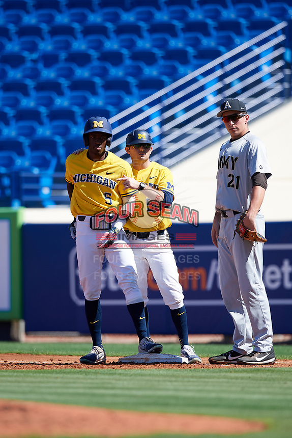 Michigan Wolverines right fielder Christan Bullock (5) talks with first base coach John Dilaura (50) as first baseman John McKenna (21) looks on during a game against Army West Point on February 17, 2018 at Tradition Field in St. Lucie, Florida.  Army defeated Michigan 4-3.  (Mike Janes/Four Seam Images)