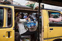 Nigeria. Enugu State. Enugu. Town center. Traffic jam. A  yellow minibus used for local transport has its side door open and is full of Igbo passengers. A traditional healer  carries on her legs an aluminium tray containing plastic bottles filled with secret medications. The woman is wearing a head tie which is a women's cloth head scarf. The head tie is used as an ornamental head covering or fashion accessory, or for functionality in different settings. Its use or meaning can vary depending on the country and/or religion of those who wear it. The head tie is called gele in Nigeria. Enugu is the capital of Enugu State, located in southeastern Nigeria. 28.06.19 © 2019 Didier Ruef