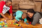 Two year old toddler boy with parents laughing as wooden blocks fall in a domino effect
