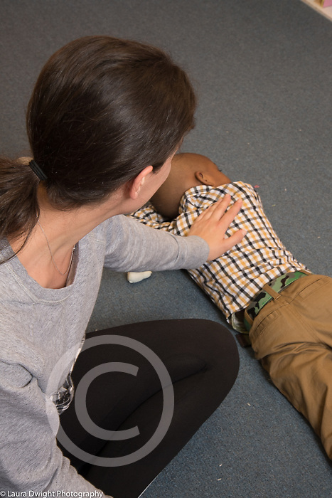 Education Preschool 3-4 year olds female teacher resting her hand on back of unhappy or tired boy