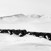 Oil barrels lying in the snow in Daneborg. Established on the east coast of Greenland in 1950, Daneborg is the base for the Sirius Patrol, a Danish navy unit which patrols and enforces Danish sovereignty in the Arctic regions of Northern and Eastern Greenland.