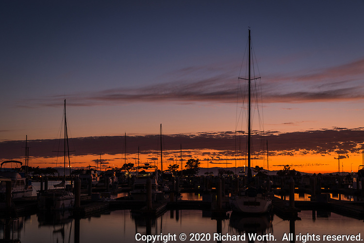 The sun sets, once a day, every day, everywhere.  Sailboats moored at the San Leandro Marina on San Francisco Bay as the sun sets on a very hot summer day.