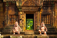 Ancient statues in 10th century Banteay Srei Shiva red sandstone temple front, in Angkor Wat Siem Reap complex, Cambodia Southeast Asia