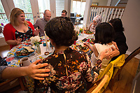 """SEATTLE, WA-APRIL 17, 2017: Hussein Saab, leads a prayer before dinner with Stefanie and Nason Fox, Anjana Agarwal, Patricia Rangel, and Greg and Charissa Pomrehn.<br /> <br /> Amanda Saab, along with her husband Hussein Saab, host a """"dinner with your Muslim neighbor"""" at the home of Stefanie and Nason (cq) Fox in Seattle, WA on a return trip April 17th 2017. The couple now live in Detroit. (Photo by Meryl Schenker/For The Washington Post)"""