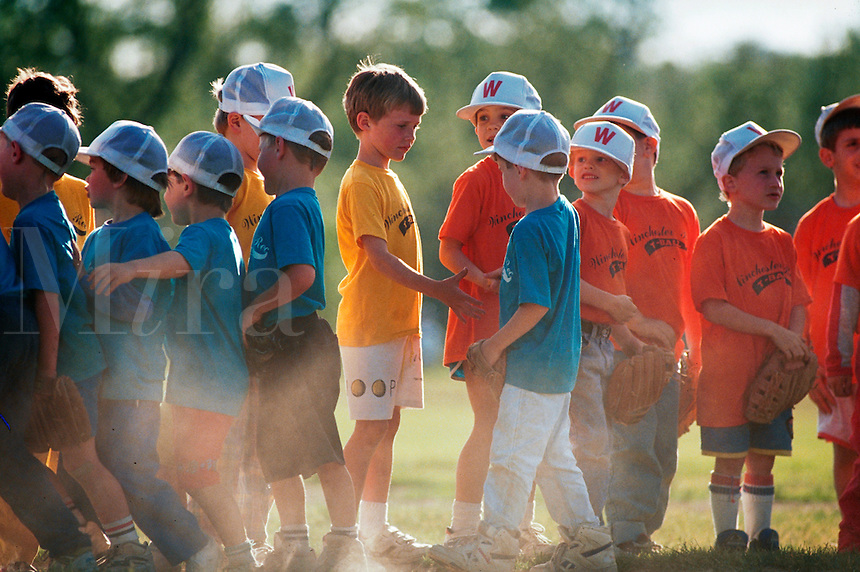 Youth baseball teams shake hands after a tee ball game.