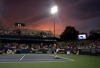 John Isner follows through on a serve during the Legg Mason Tennis Classic at the William H.G. FitzGerald Tennis Center in Washington, DC.  Unseeded Xavier Malisse defeated American John Isner in three sets in a thunderstorm delayed evening session.