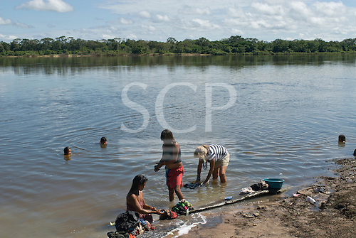 Xingu Indigenous Park, Mato Grosso State, Brazil. Aldeia Tuiarare (Kaiabi). Sue washing clothes with women of the village.