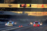 Nov. 10, 2012; Pomona, CA, USA: NHRA funny car driver John Force (left) races alongside Jim Head during qualifying for the Auto Club Finals at at Auto Club Raceway at Pomona. Mandatory Credit: Mark J. Rebilas-