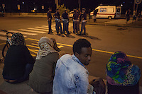 Italy. Lombardy Region. Como. Homeless african migrants seat on the ground at night in the San Giovanni railway station. A group of Italian policemen stand in the middle of the road. The italian Red Cross from Como has provided an ambulance with some volunteers and offers medical consultation to the migrants. 10.08.2016 © 2016 Didier Ruef