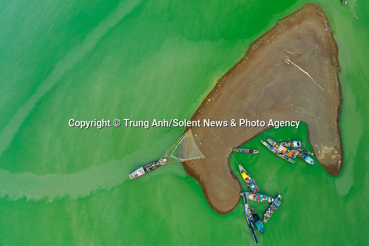 Fishing boats sail on a green lake filled with algae.  Fishermen set sail across the vibrant green coloured water, which contrasts with the dark shoreline.<br /> <br /> They collect fish, such as the suckermouth catfish, as they are surrounded by green algae which appears every summer.  Amateur photographer Trung Anh pictured the fishing boats on the Tri An Lake, Vietnam.  SEE OUR COPY FOR DETAILS.<br /> <br /> NOTE:  Genuine colour of algae filled water - photographer has shared a reference 'snap' showing his drone remote unit displaying the green water at the time he was flying the drone.<br /> <br /> Please byline: Trung Anh/Solent News<br /> <br /> © Trung Anh/Solent News & Photo Agency<br /> UK +44 (0) 2380 458800