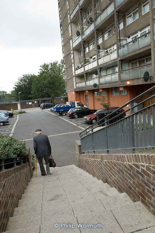 An elderly man walks to his home in a high rise block on the Brindley Estate, North Paddington, London.
