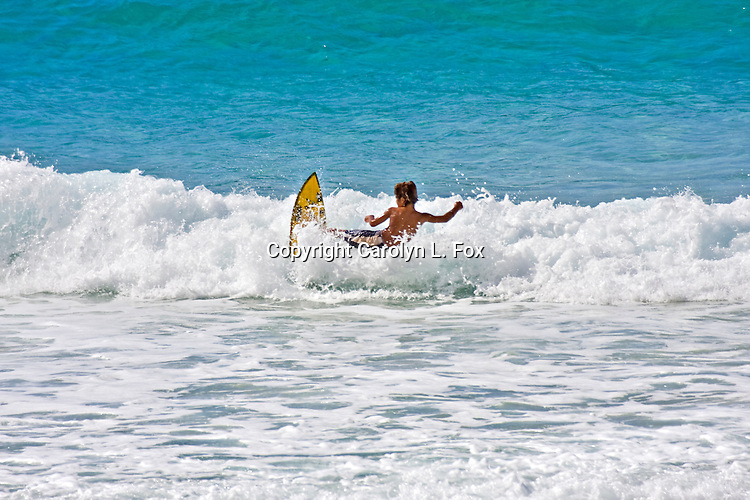 A young boy rides a surfboard.