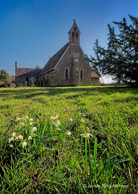 The exterior of St. Lawrence' Curch, Tubney, Oxfordshire, with snowdrops flowering in February sunshine. The church was the only Protestant church designed by Augustus Pugin and was consecrated in 1847