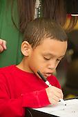 MR / Schenectady, NY. Zoller Elementary School (urban public school). Kindergarten inclusion classroom. Student (boy, 6, African American & Puerto Rican American) writes numbers on erasable worksheet during math lesson. MR: War15, Car38. ID: AM-gKw. © Ellen B. Senisi.