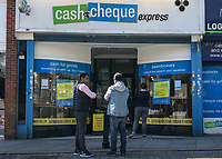 High Wycombe, England 20/04/2020 -<br /> People wait outside a cash & cheque express shop in High Wycombe during the COVID-19 pandemic lockdown as the UK Government advice to maintain social distancing and minimise time outside in High Wycombe on 20 April 2020. Photo by PRiME Media Images / Andy Rowland.