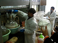 A bag of 'new product' is seen whilst a worker prepares a drug similar to MDPV at a laboratory belonging to CEC Limited, a company which exports the legal high to Great Britain, Pudong, Shanghai, China, 08 April 2010.