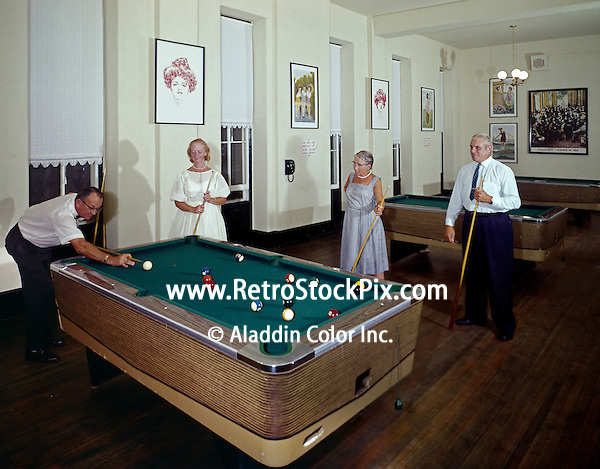 Well dressed couple in the Congress Hall Hotel game room shooting pool. 1960's