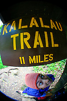 A young woman stands beneath the Kalalau Trail sign at the trailhead, Ke'e Beach, Kaua'i.