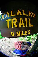 A young woman stands beneath the Kalalau Trail sign at the trailhead, Ke'e Beach, Kaua'i.