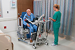 Healthcare professional helps move patient in hospital using KCI device.