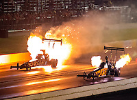 Oct 14, 2016; Ennis, TX, USA; NHRA top fuel driver Scott Palmer (left) has an engine fire alongside Troy Buff during qualifying for the Fall Nationals at Texas Motorplex. Mandatory Credit: Mark J. Rebilas-USA TODAY Sports