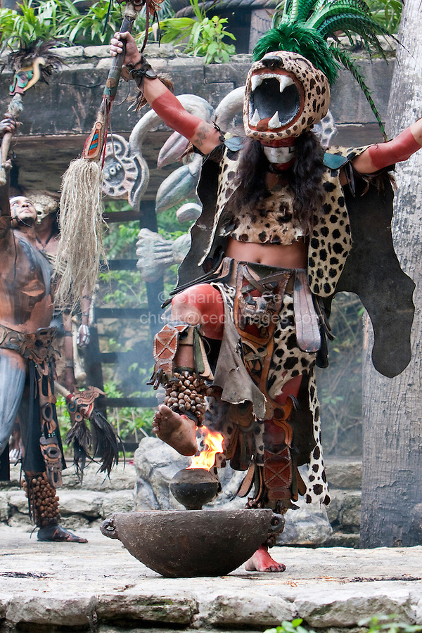 Mayan Dancer Representing Ek Balam (Jaguar), a warrior god, places his foot on the sacred fire.  Xcaret, Riviera Maya, Yucatan, Mexico.
