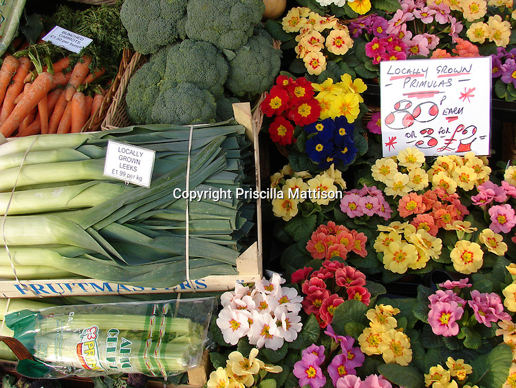 Vegetables and flowers are for sale at a Cotswolds produce stand.