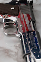 Handgun on marble surface with American flag reflected in barrel<br />