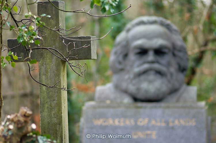 A cross on a grave opposite the tomb of Karl Marx in Highgate Cemetery, London.