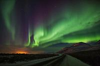 The aurora swirls over the dalton highway in Atigun Canyon, Brooks Range, Arctic, Alaska.