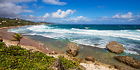 Deserted Cattlewash Beach with rocks in the turquoise water, lush vegetation, golden sand, and a blue sky with dramatic clouds, in Barbados Island