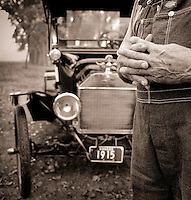The clasped hands of a senior male farmer in bib overalls, posed before a vintage 1915 car.