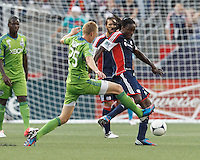 New England Revolution midfielder Shalrie Joseph (21) attempts to control the ball as Seattle Sounders FC midfielder Andy Rose (25) pressures. In a Major League Soccer (MLS) match, the New England Revolution tied the Seattle Sounders FC, 2-2, at Gillette Stadium on June 30, 2012.